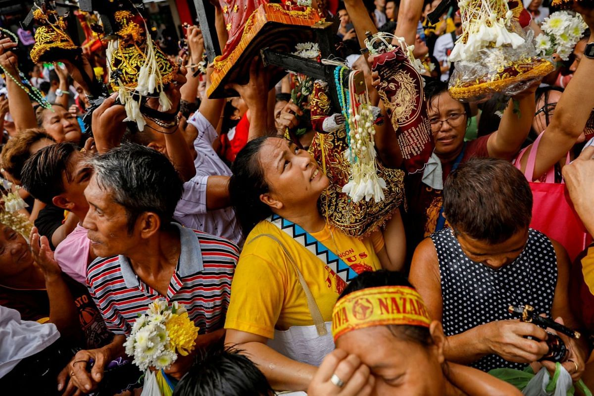 Filipino devotees carry replicas of the Black Nazarene to be blessed with holy water during a parade two days before the annual procession to celebrate its feast day in Quiapo, Manila, Philippines, Jan 7, 2020.