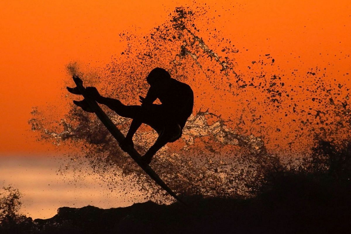 A surfer takes some air off a wave while surfing after sunset in Cardiff, California, U.S., Jan 7, 2020.