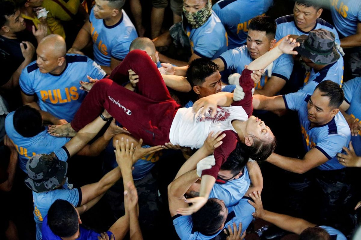 A Filipino devotee is carried by police officers outside the Quiapo church after she fainted during the Black Nazarene feast day in Manila, Philippines, Jan 9, 2020.