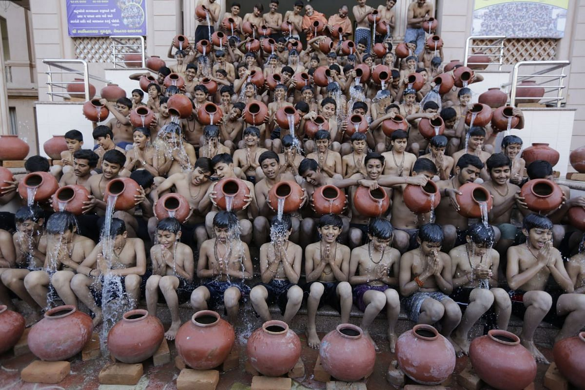 Indian students of Swaminarayan Gurukul perform a ritualistic bath called Magh Snan in Ahmadabad, India, Jan. 9, 2020. Magh Snan is performed during the auspicious Hindu calendar month of Magh and is believed to absolve devotees of their sins. Studen