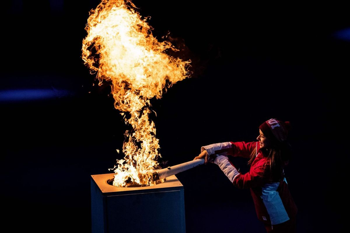 Gina Zehnder, the youngest representative of the Swiss Team, lights the Olympic cauldron with the Olympic torch during the opening ceremony of the Lausanne 2020 Winter Youth Olympic Games in Switzerland on Jan 9, 2020.