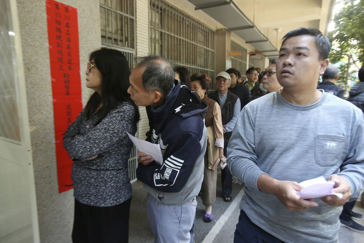 Taiwanese people line up to cast their ballot at a polling station in New Taipei City on Jan 11, 2020.