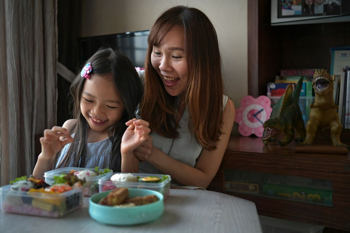 Stay-at-home mother Toh Geok Kung spending time with her daughter Myra during a meal.
