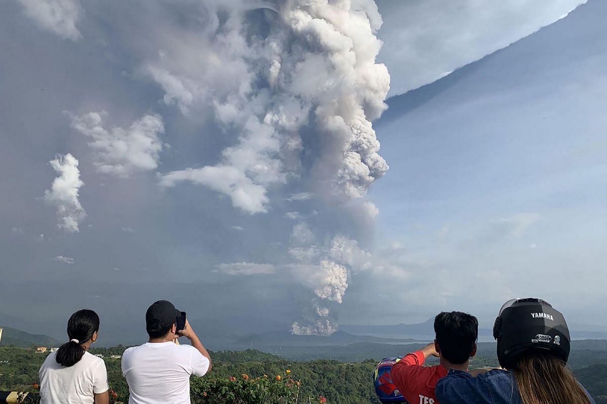 People take photos of a phreatic explosion from the Taal volcano as seen from the town of Tagaytay in Cavite province, southwest of Manila, on January 12, 2020. PHOTO: AFP