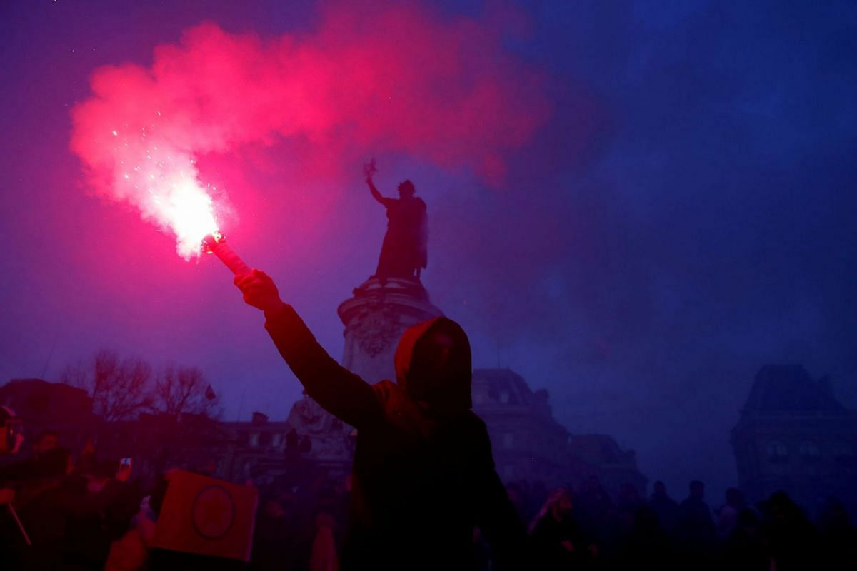 A protester holds a flare during a demonstration of French labour union members and workers, as France faces its 38th consecutive day of strike against French government's pensions reform plans, in Paris, France January 11, 2020. PHOTO: REUTERS