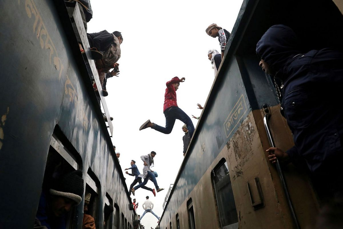 People jump between trains, who has come to attend at the final prayer of Bishwa Ijtema, which is considered the world's second-largest Muslim gathering after Haj, in Tongi, outskirts of Dhaka, Bangladesh, January 12, 2020. PHOTO: REUTERS