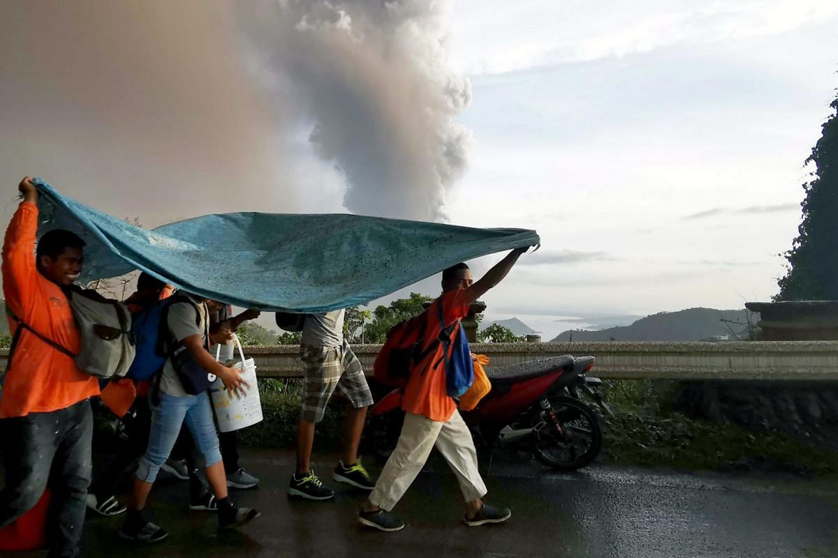 People take cover under a large plastic sheet as a column of ash spews from erupting Taal volcano over Tagaytay city, Philippines on Jan 12, 2020.