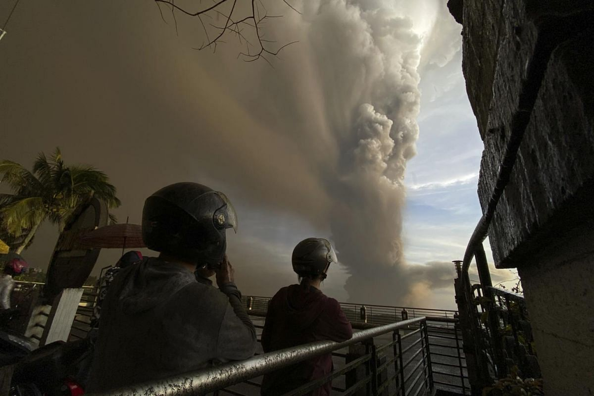 People watch plumes of smoke and ash rise as Taal volcano erupts, in Tagaytay, Cavite province, outside Manila, Philippines on Jan 12, 2020.