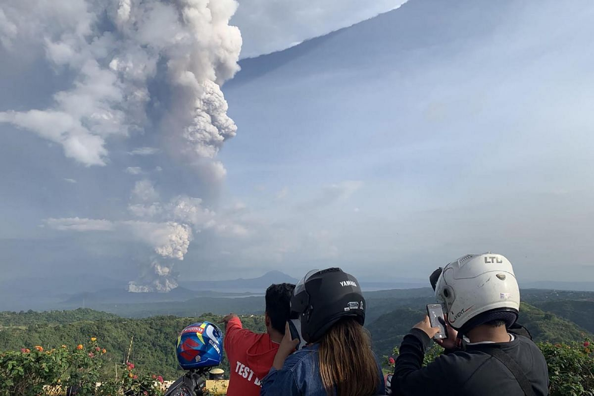 People take photos of a phreatic explosion from the Taal volcano as seen from the town of Tagaytay in Cavite province, south-west of Manila on Jan 12, 2020.