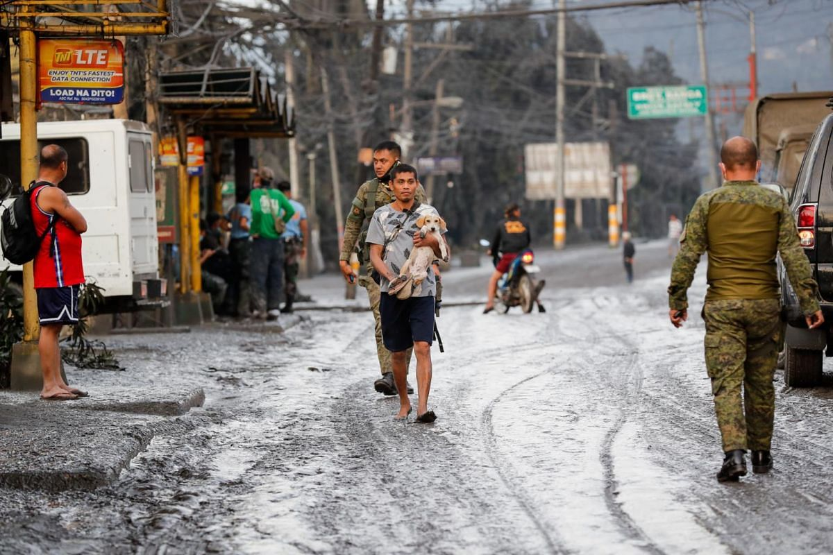A man carries his dog after a volcano eruption in Talisay, Batangas, Philippines on Jan 13, 2020.