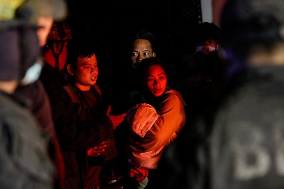 A woman holds on to her child before boarding a rescue vehicle after a volcano eruption in Talisay, Batangas, Philippines on Jan 13, 2020.