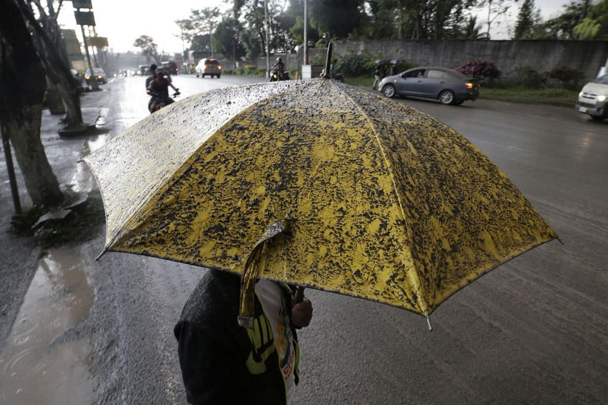 A man uses an umbrella to shield himself from ashfalls as Taal volcano erupts, in Tagaytay, Cavite province, outside Manila, Philippines on Jan 12, 2020.