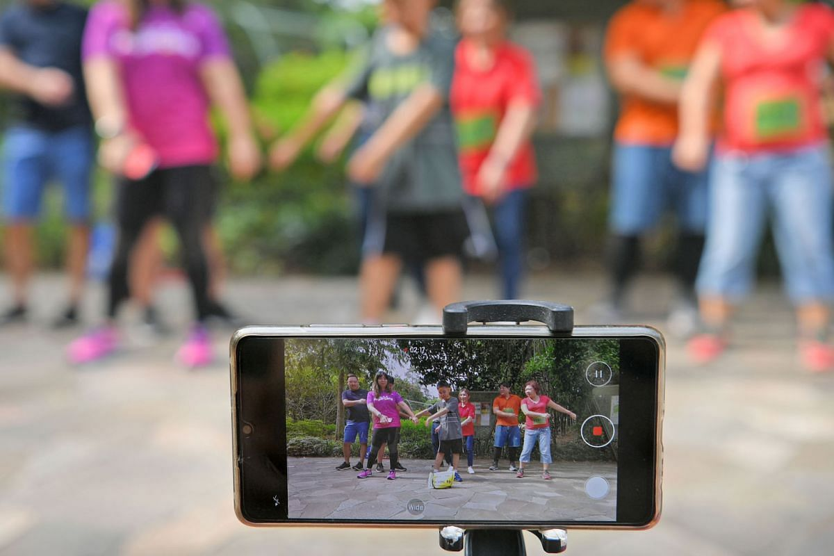 A team shooting a video of themselves dancing at the Singapore Botanic Gardens. Teams had to complete two tasks at each location - solving a puzzle using their senses and creating a short video.