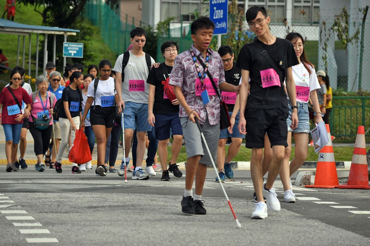 Participants and volunteers on the way to Caldecott MRT station to start the Amazing Race-style fund-raising event race on Saturday. The volunteers underwent half an hour of training to learn how to effectively guide a person with vision loss.