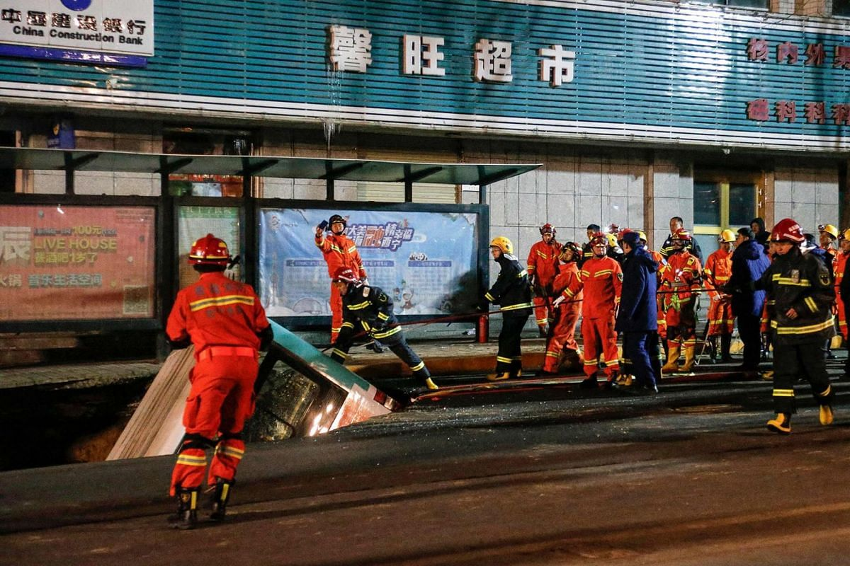 This photo taken on January 13, 2020 shows Chinese rescuers preparing to lift a bus after a road collapse in Xining in China's northwestern Qinghai province. An enormous sinkhole swallowed passers-by and a public bus in northwest China, injuring fift