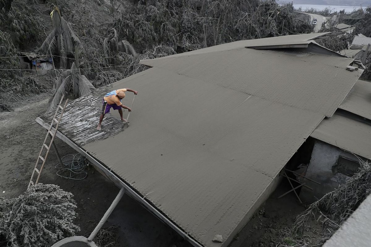 A resident clears volcanic ash from his roof in Laurel, Batangas province, southern Philippines on Tuesday, Jan. 14, 2020. PHOTO: AP