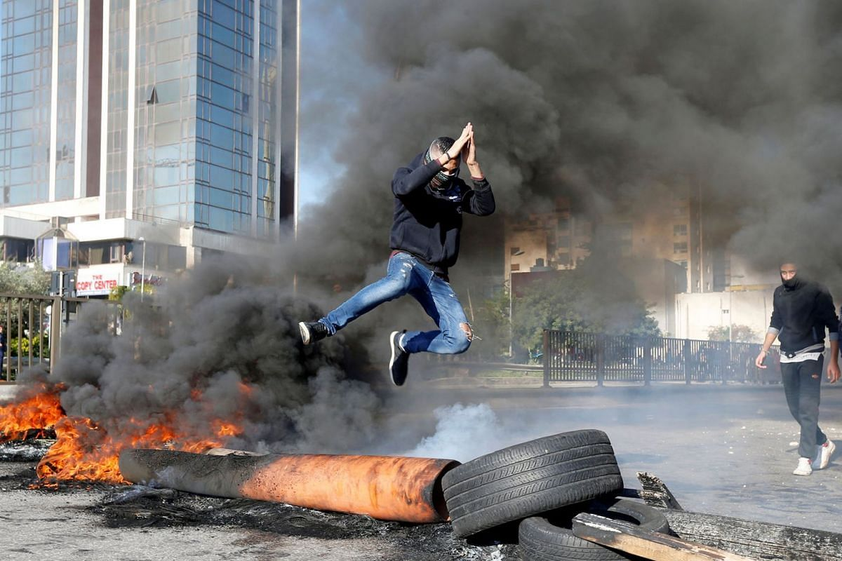 A protestor jumps over a burning barricade during a protest over economic hardship and lack of new government in Beirut, Lebanon January 14, 2020. PHOTO: REUTERS