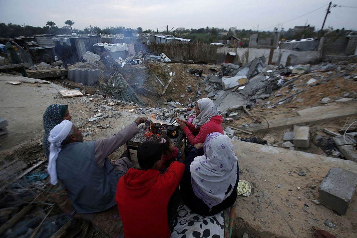 Family members of Hamouda Abu Amra gather around campfire to get warm in the winter's cold outside their destroyed house in Khan Younis, southern Gaza Strip on Jan. 14, 2020. PHOTO: AP