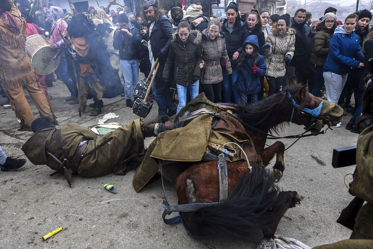 A participant falls with his horse during the traditional mask burning on the second day of a carnival celebration marking the Orthodox St. Vasilij Day in the village of Vevcani, some 170 km from Skopje, Republic of North Macedonia, Jan 14,  2020. PH
