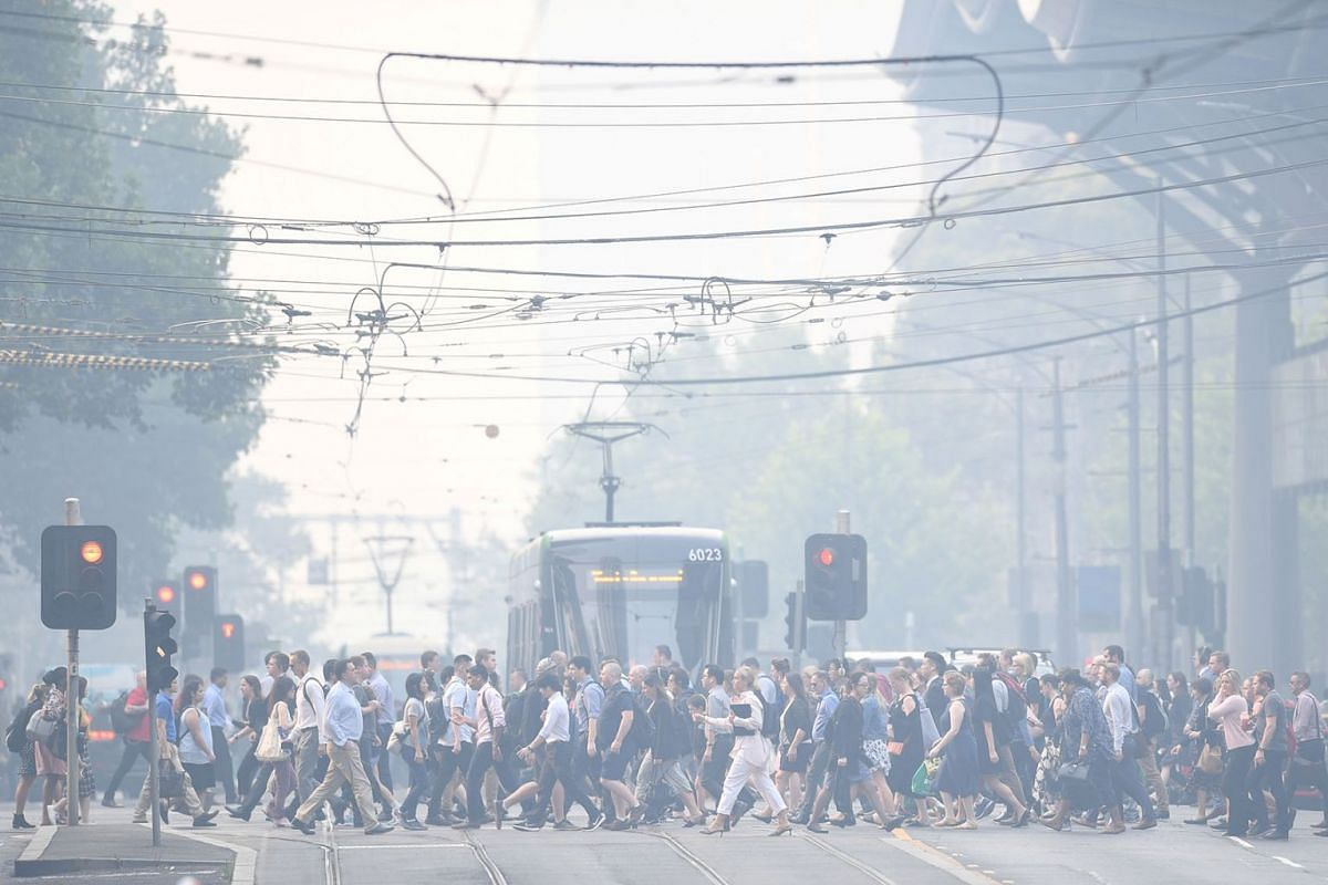 Morning commuters are seen through smoke haze from bushfires in Melbourne, Australia, January 14, 2020. PHOTO: AAP IMAGE VIA REUTERS