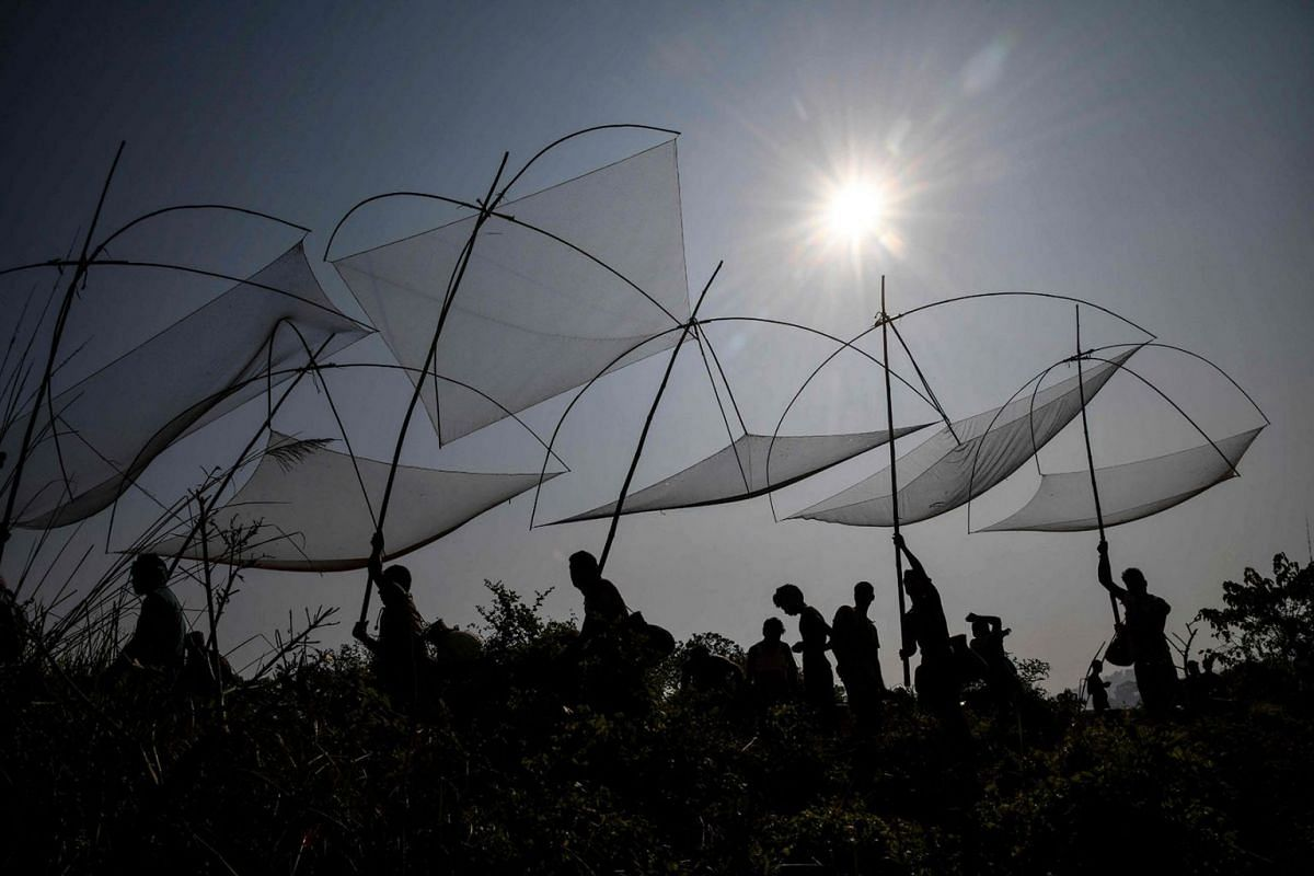 Villagers carry their fishing nets as they take part in a community fishing event during Bhogali Bihu harvest celebrations at Goroimari Lake in Panbari, some 50 kms from Guwahati, on January 14, 2020. PHOTO: AFP