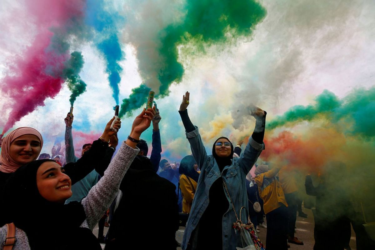 Iraqi women wave colored smoke candles during the festival of colors, in the holy Shi'ite city of Najaf, Iraq January 15, 2020. PHOTO: REUTERS