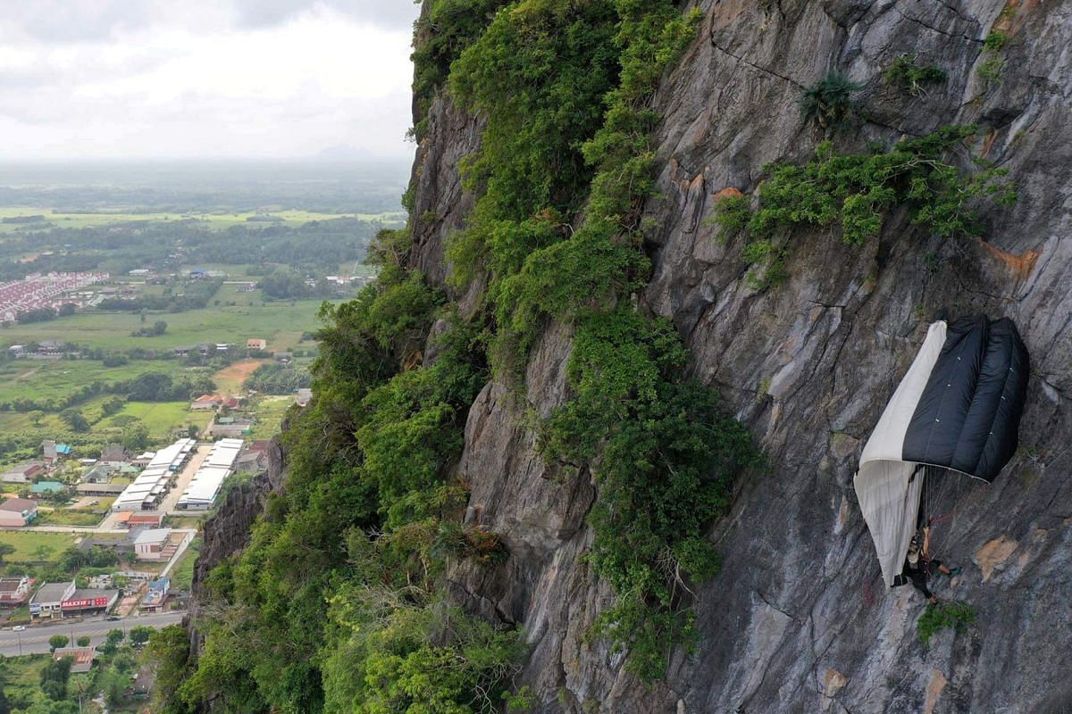 A BASE jumper hangs, snagged from his parachute, after being blown into the Khao Thalu cliff, Khuha Sawan, Mueang Phatthalung District, Thailand January 13, 2020 in this image obtained from social media. PHOTO: FREEDOM TEAM DRONE VIA