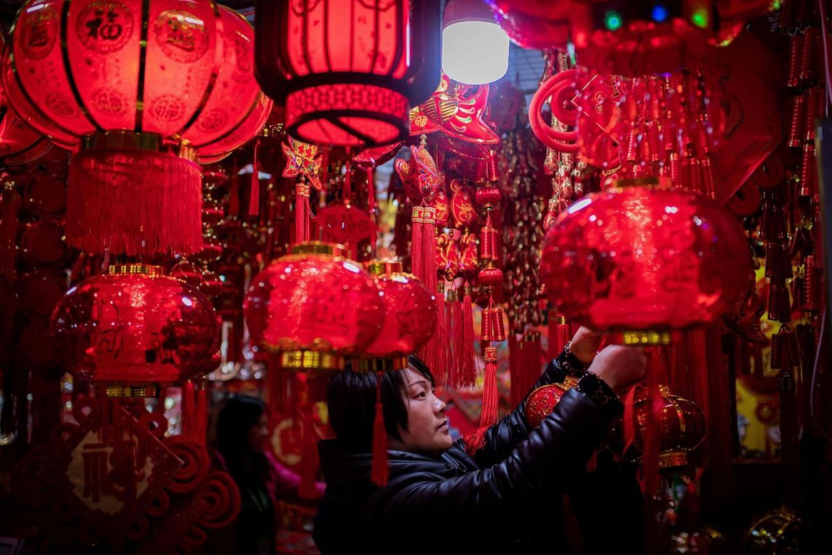 A vendor adjusts lanterns at her stall at a market in Beijing on January 15, 2020, ahead of the Lunar New Year of the Rat. PHOTO: AFP