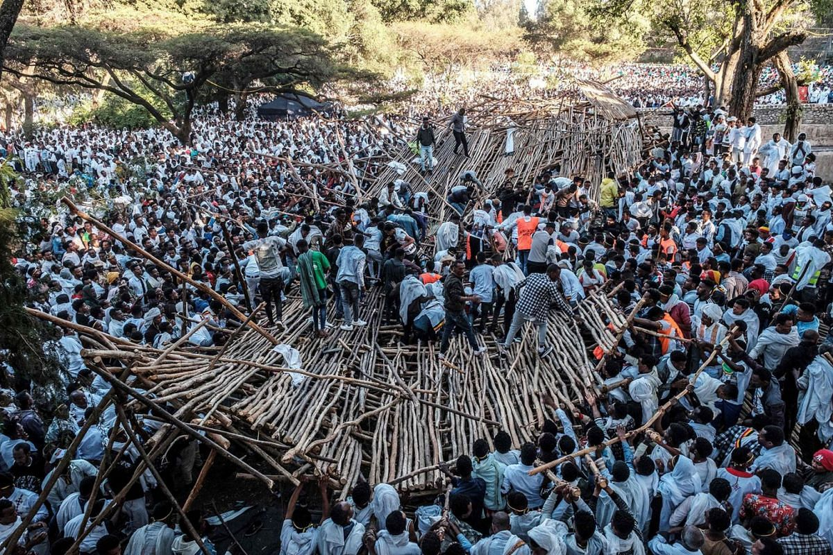 A crowd removes scaffoldings of a structure that collapsed, trapping and injuring dozens of people, during the celebration of Timkat, the Ethiopian Epiphany, in Gondar, Ethiopia, on January 20, 2020. PHOTO: AFP