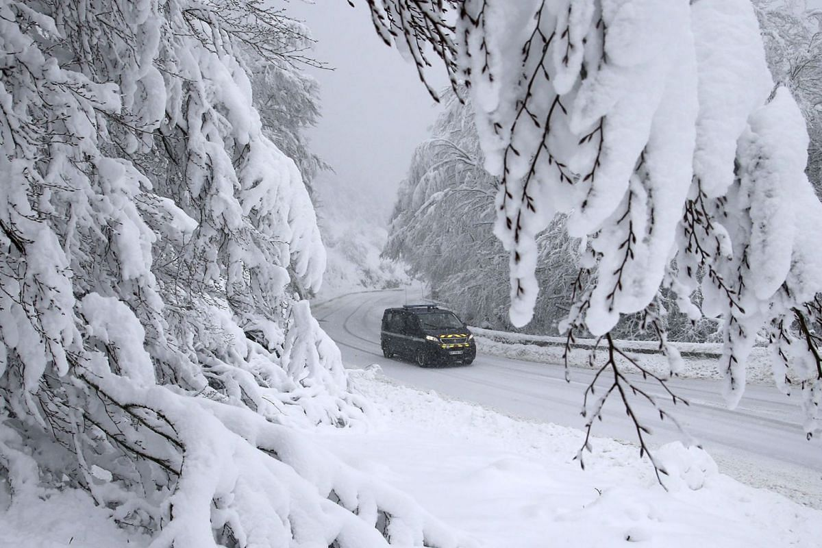 A police vehicle drives on a snow-covered road at the Vizzavona pass, close to Bocognano, after heavy snowfall and strong winds due to Gloria storm on the French Mediterranean island of Corsica, on January 20, 2020. PHOTO: AFP