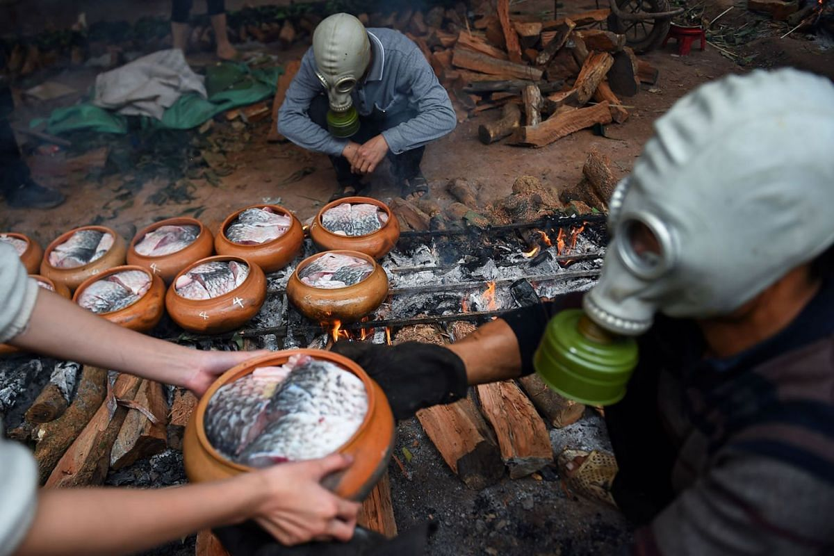 Men wear gas masks while cooking fish in claypot over wood fire in Ha Nam province on January 21, 2020 ahead of the Lunar New Year. The braised fish is a popular delicacy for the Lunar New Year or Tet season in Vietnam's north with each pot selling 1