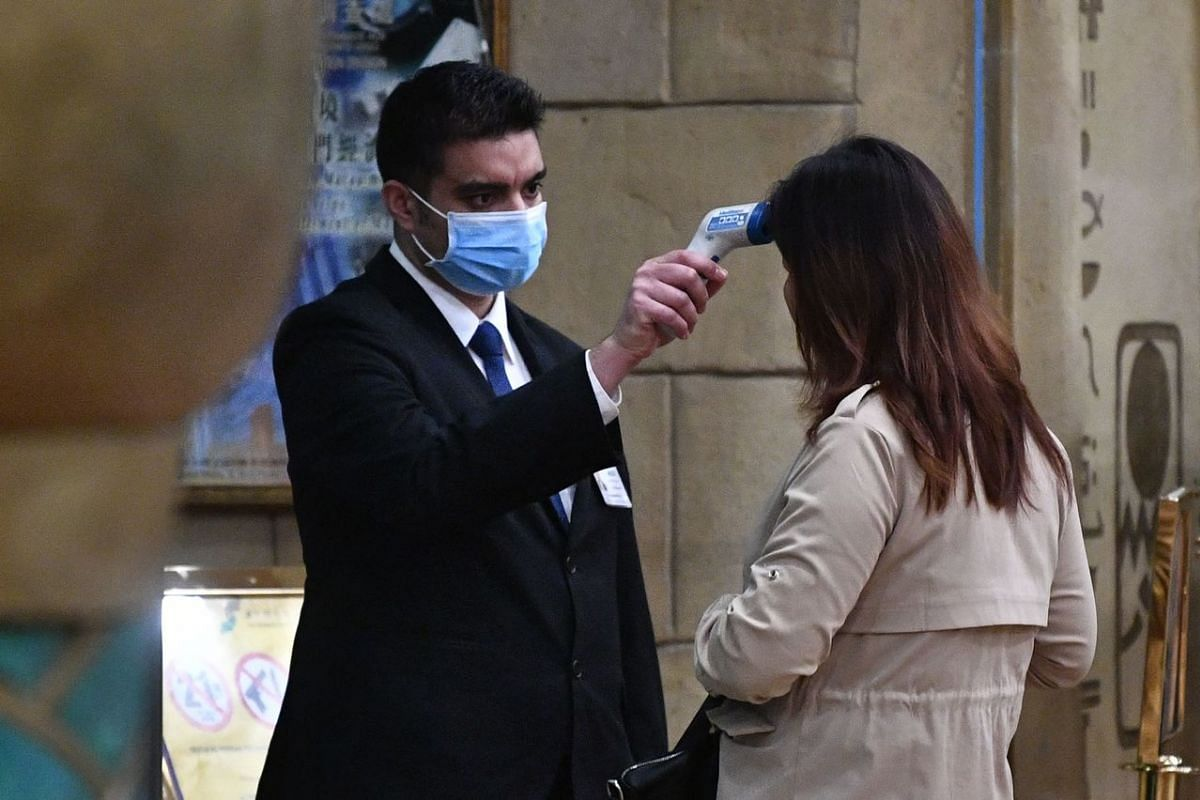 A staff member checks the temperature of a guest entering the casino of the New Orient Landmark hotel in Macau on Jan 22, 2020.