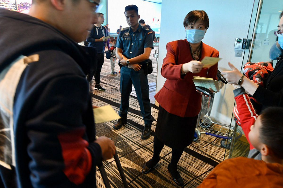 An airport staff member distributing health advisory pamphlets to passengers who had just disembarked from a flight from Hangzhou, at Changi Airport.