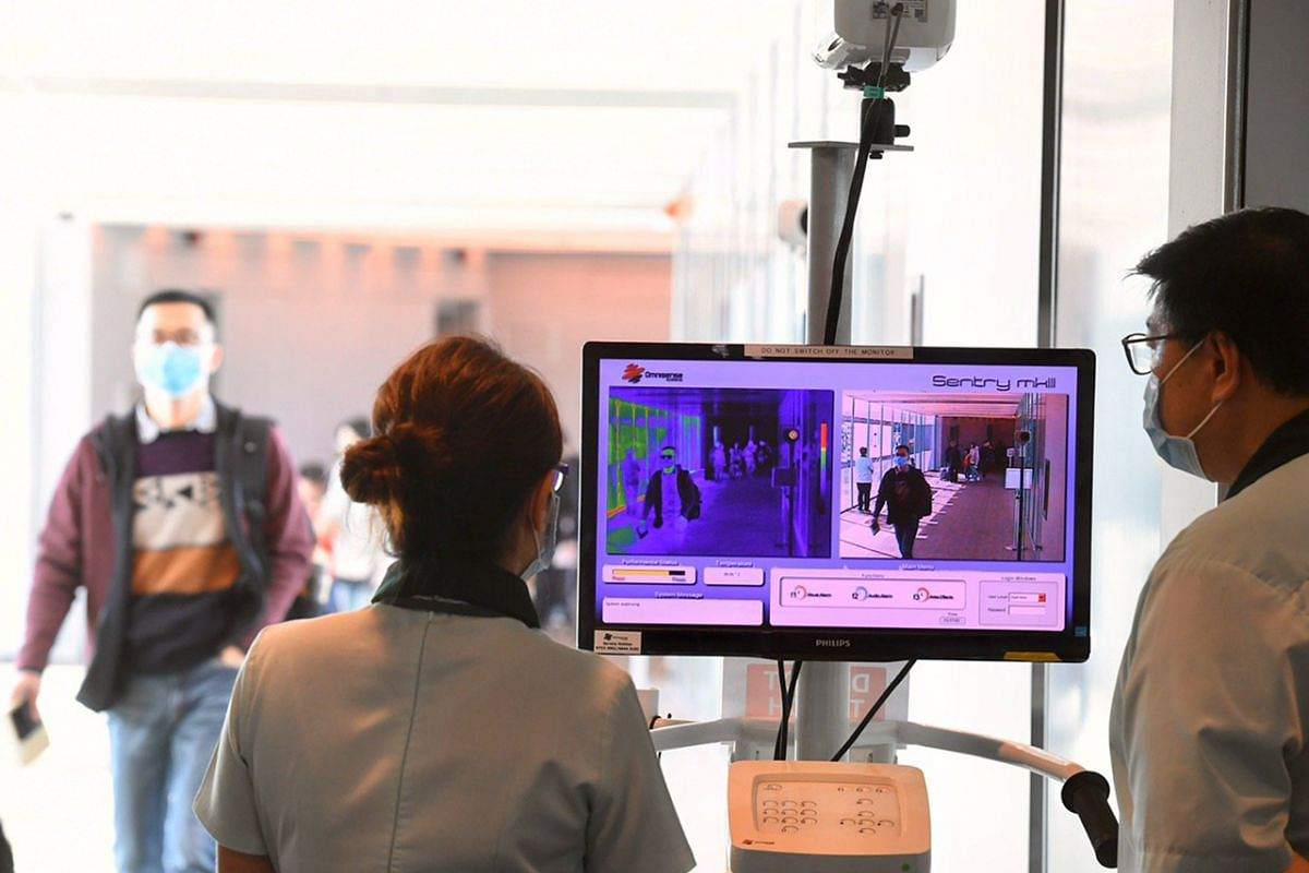 Passengers arriving at Changi Airport Terminal 3 on a flight from Hangzhou going through a thermal scanner.