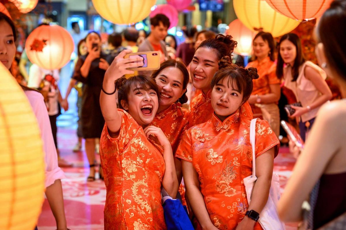Visitors in traditional cheongsams take a selfie in a shop decorated for the Chinese Lunar New Year in Bangkok, on Jan 24, 2020.