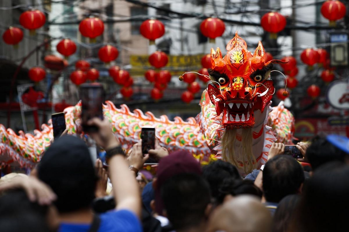 People watch a dragon dance performance during celebrations to mark the Chinese Lunar New Year in Manila on Jan 25, 2020.