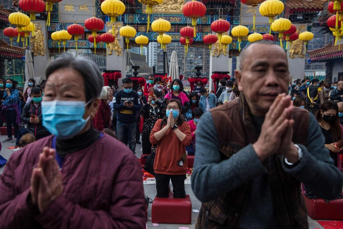 People wear masks as they pray at a temple on the first day of the Chinese Lunar New Year in Hong Kong on Jan 25, 2020.