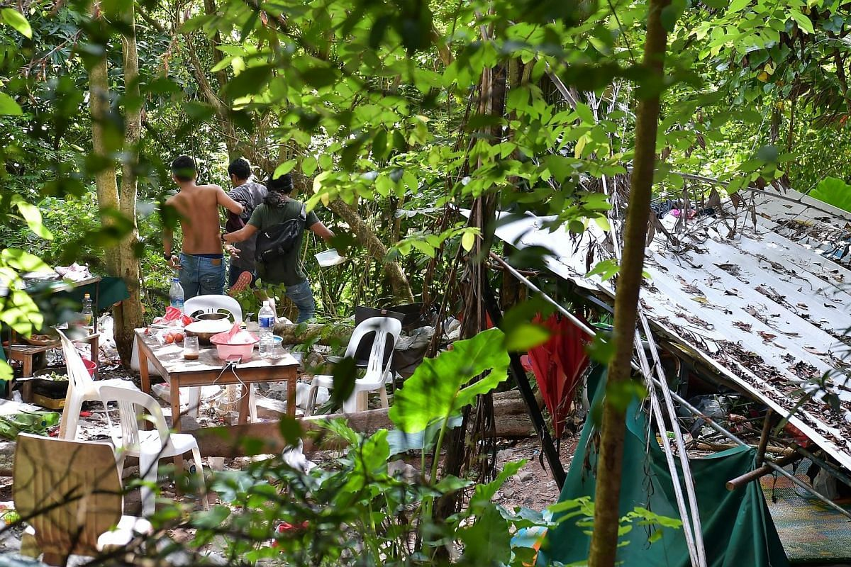 Suspected illegal immigrants fleeing down the slope from their forested hideout - located between the KJE and a slip road leading to Woodlands - after they spotted the ST team on Dec 27 last year. In their escape, they left their mobile phones on the