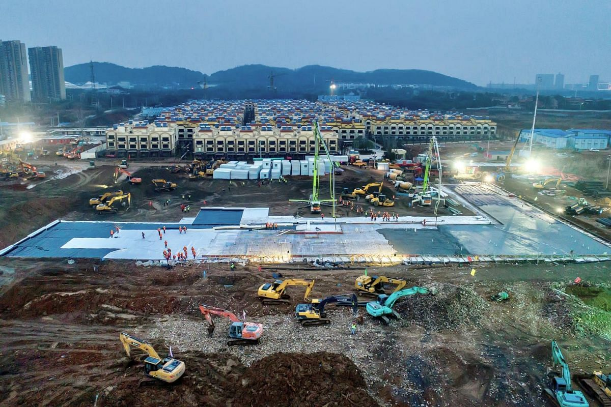 """Excavators and workers are seen at the construction site of the new Huoshenshan Hospital on Jan 27, 2020. A second hospital, called Leishenshan, or """"thunder-god mountain"""", with 1,600 beds, is scheduled to be completed on Wednesday (Feb 5,2020)."""