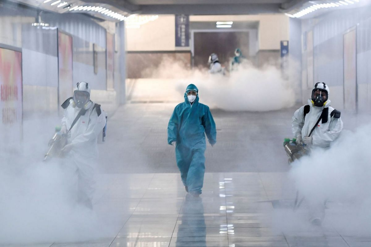 Volunteers in protective suits disinfect a railway station as the country is hit by an outbreak of the new coronavirus, in Changsha, Hunan province, China Feb 4, 2020.