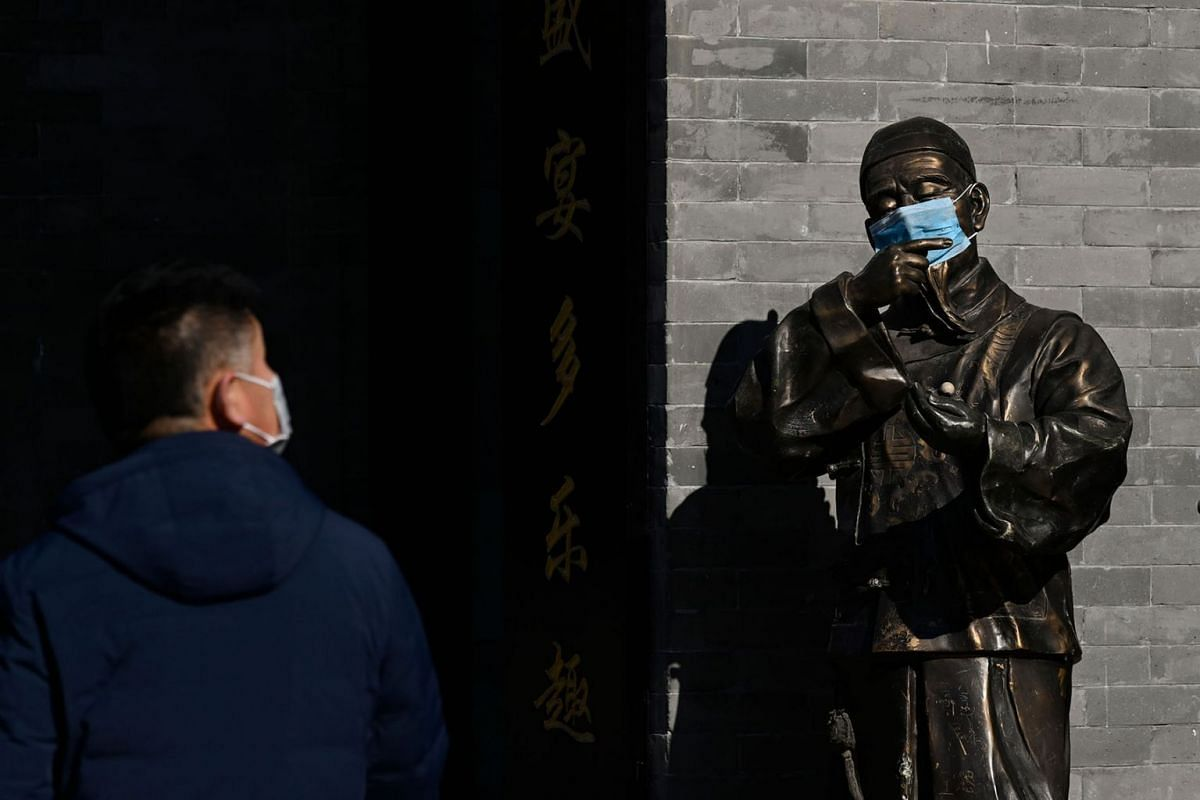 A bronze statue wearing a mask is seen at the entrance of a shop along a business street in Beijing on February 4, 2020. The number of total infections in China's coronavirus outbreak has passed 20,400 nationwide with 3,235 new cases confirmed, the