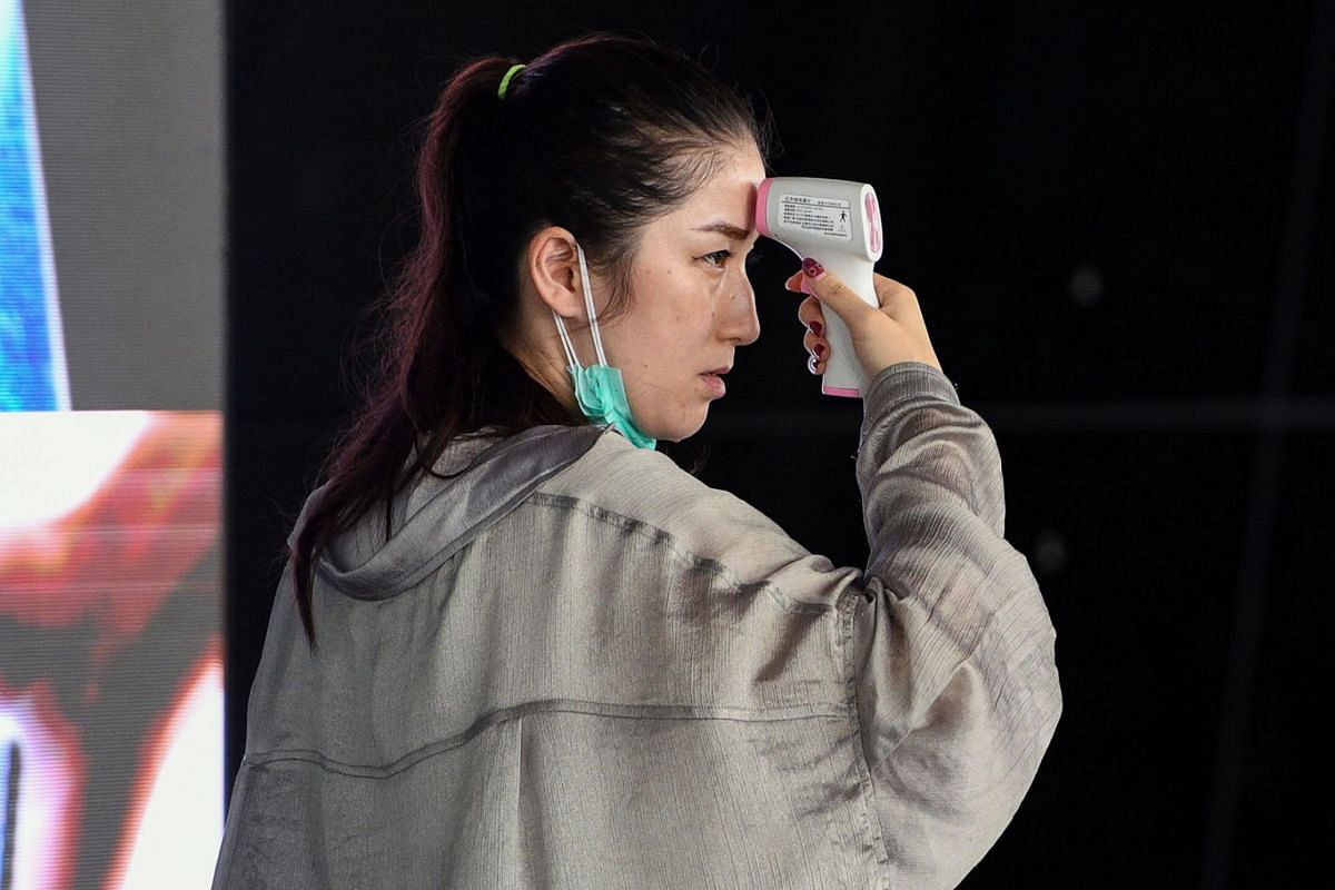 A passenger checks herself with a digital infrared forehead thermometer measurement device at Kuala Lumpur International Airport, Malaysia, on Feb 4, 2020.