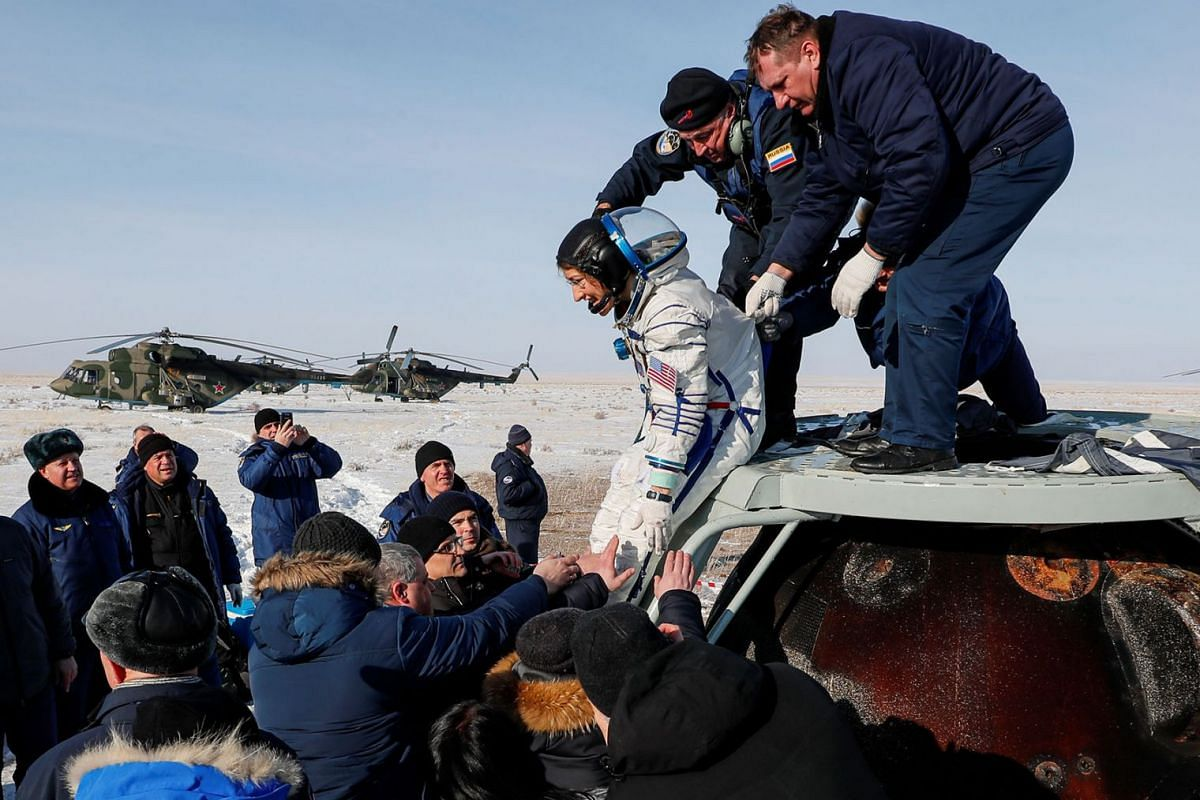 Specialists help NASA astronaut Christina Koch shortly after landing of the Russian Soyuz MS-13 space capsule in a remote area southeast of Zhezkazgan in the Karaganda region of Kazakhstan, Feb 6, 2020.