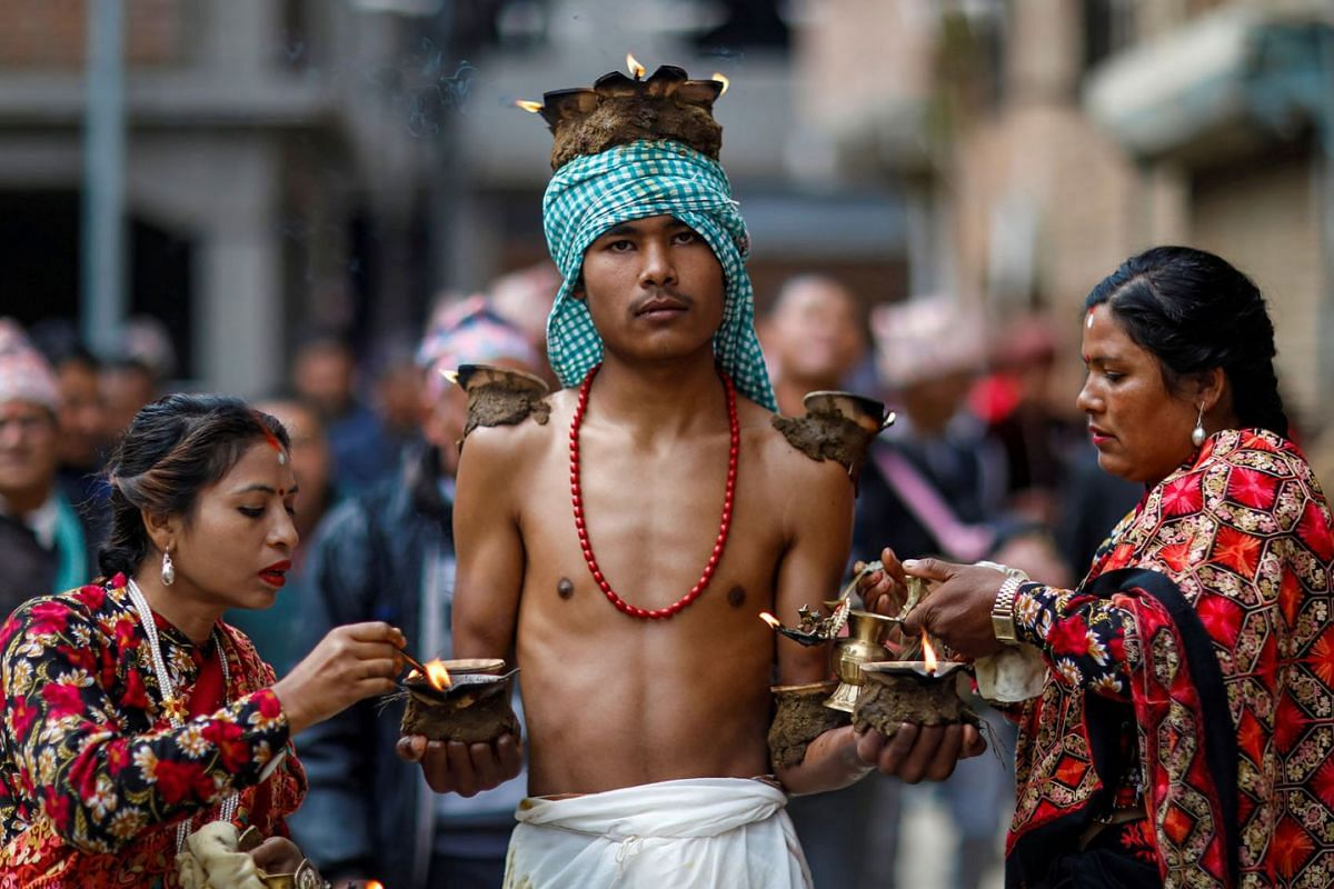 Devotees with lit oil lamps perform religious rituals during the Swasthani Brata Katha festival at Thecho in Lalitpur, Nepal, Feb 6, 2020.