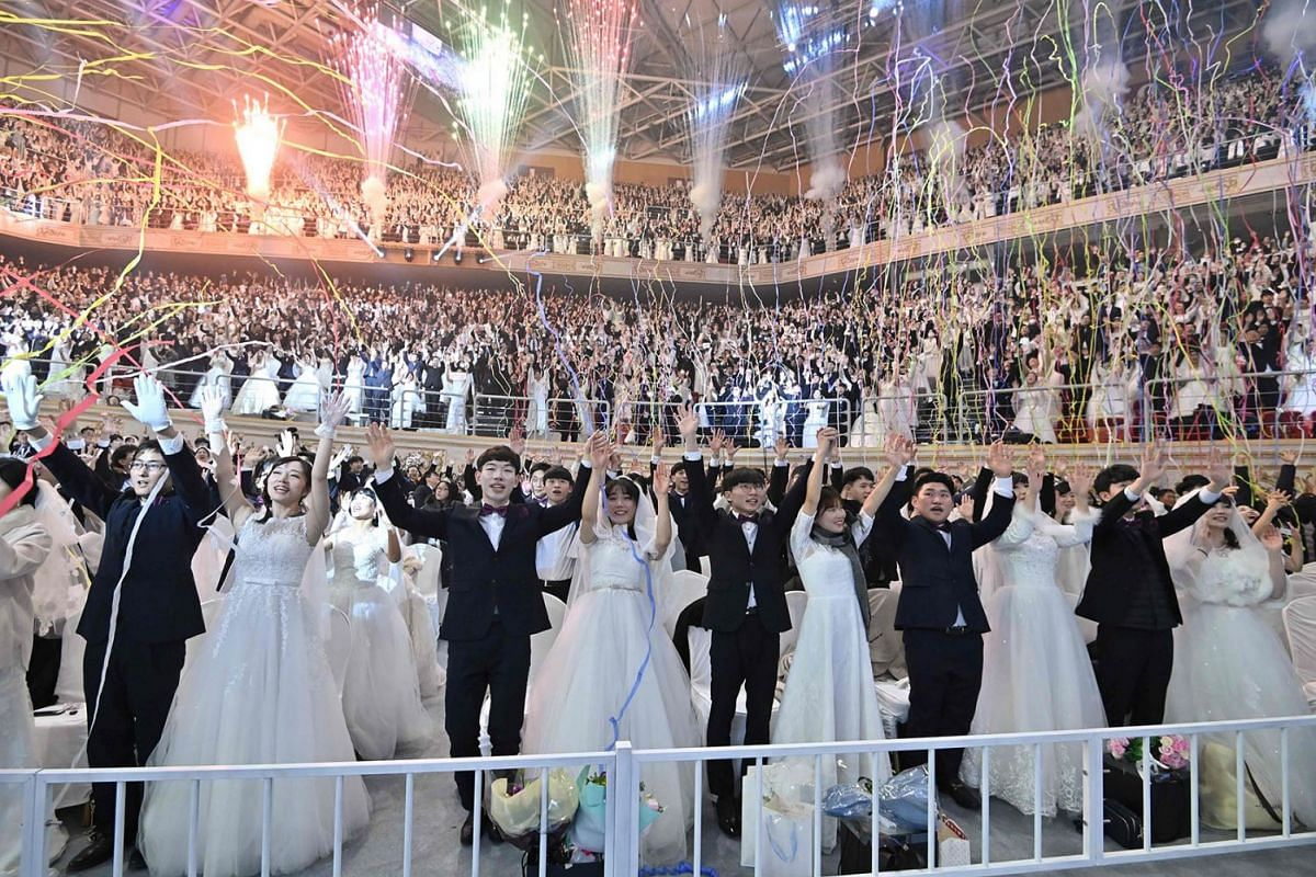 Couples cheer during a mass wedding ceremony organised by the Unification Church at Cheongshim Peace World Center in Gapyeong, South Korea, Feb 7, 2020. Thousands of Unification Church couples married at a mass wedding to mark the eighth anniversary