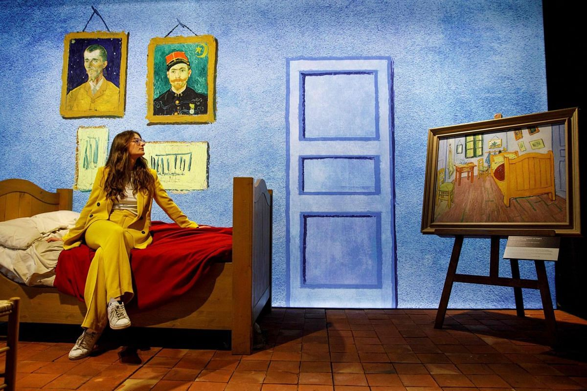 An employee poses with a re-created scene depicting a bedroom belonging to Dutch artist Vincent Van Gogh, during a photocall to promote the 'Meet Vincent van Gogh' exhibition, at the South Bank centre in London on Feb 6, 2020.