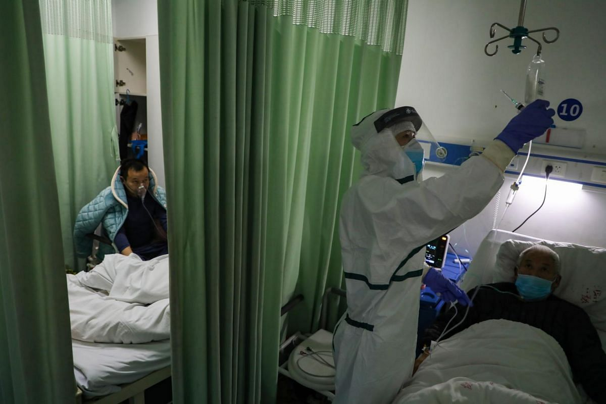 A nurse helping a patient with an intravenous drip in the isolation ward for coronavirus patients in a hospital in Wuhan, Hubei province, on Feb 6, 2020.