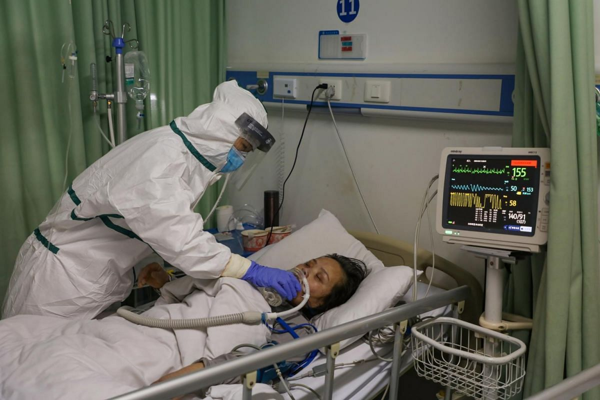 A nurse helping a patient drink water in the isolation ward in a hospital in Wuhan, Hubei province, on Feb 6, 2020.