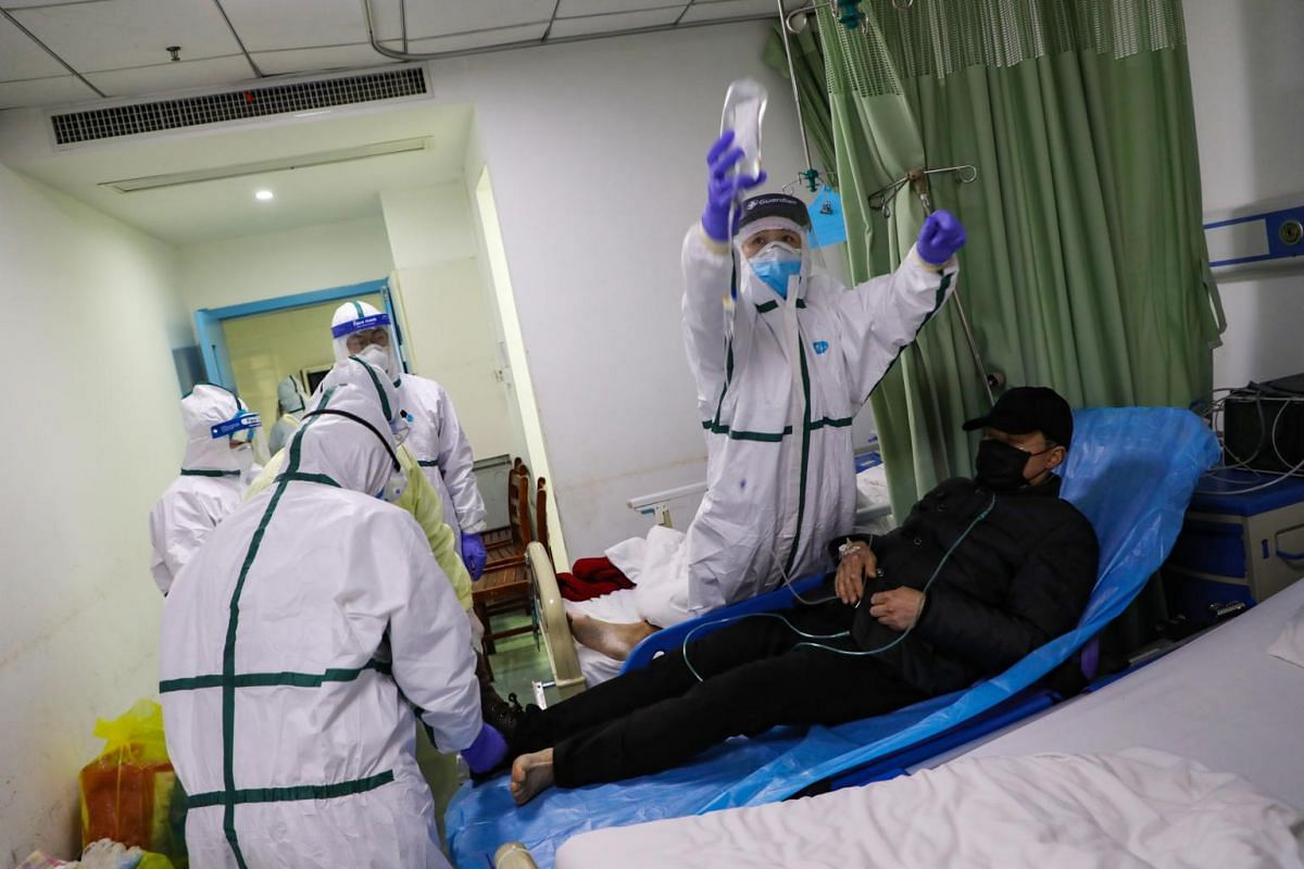 Medical staff helping to calm a coronavirus patient who had just been moved into the isolation ward in a hospital in Wuhan, Hubei province, on Feb 6, 2020.