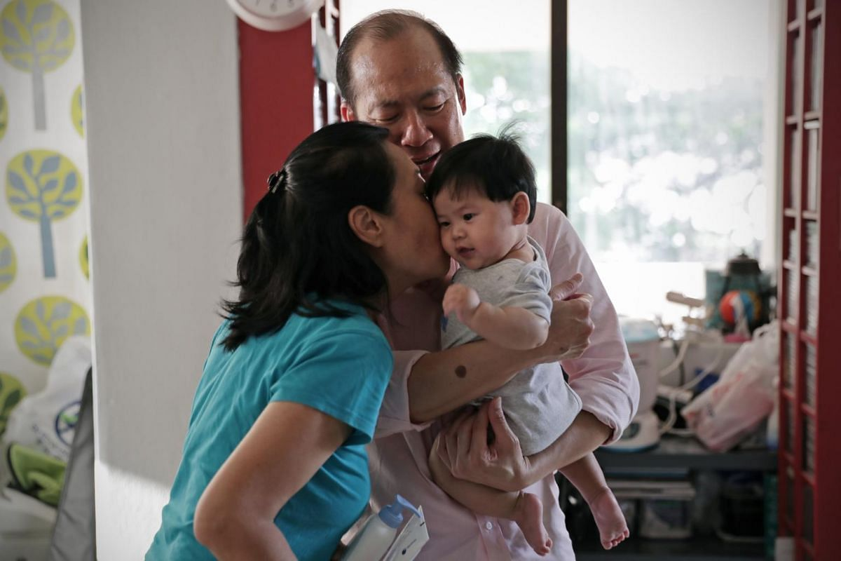 Madam Janet Lee (in blue) gives a kiss to their god-grandson as she helps to take care of the five-month-old for her god-daughter, who has to work in the day.